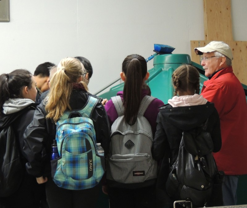 Rod MAcVicar shows students coho at Mossom Creek Education Centre